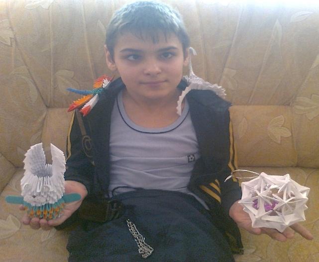 Мальчик показывает сделанную стрекозу, скорпиона, шар и зайчика